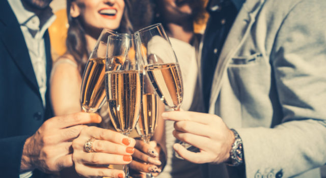 Men and women celebrating birthday or new years party while clinking glasses with sparkling wine